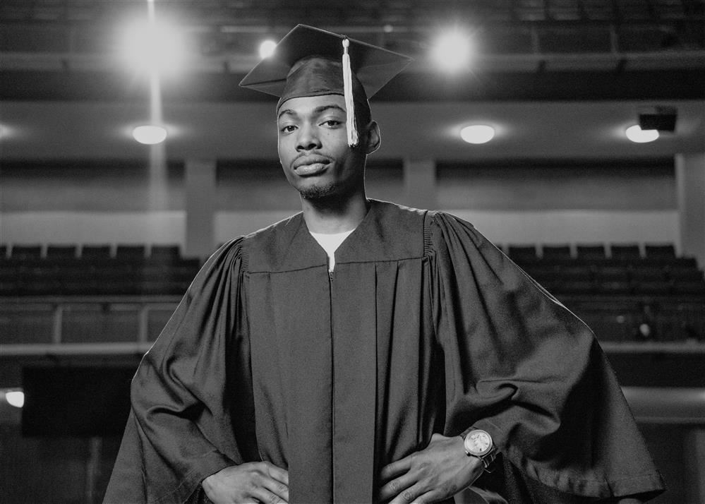 Image of student standing in theater wearing a cap and gown.