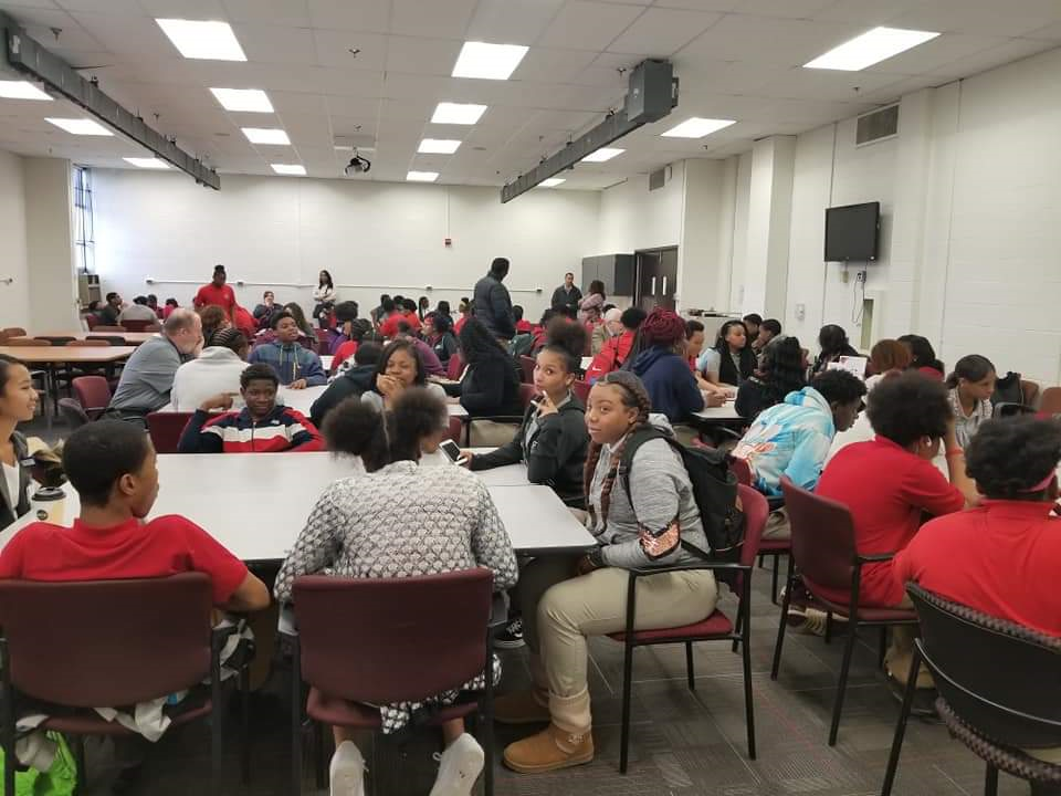 Image of students, future student and family gathered in conference room at DCPHS at Northwestern