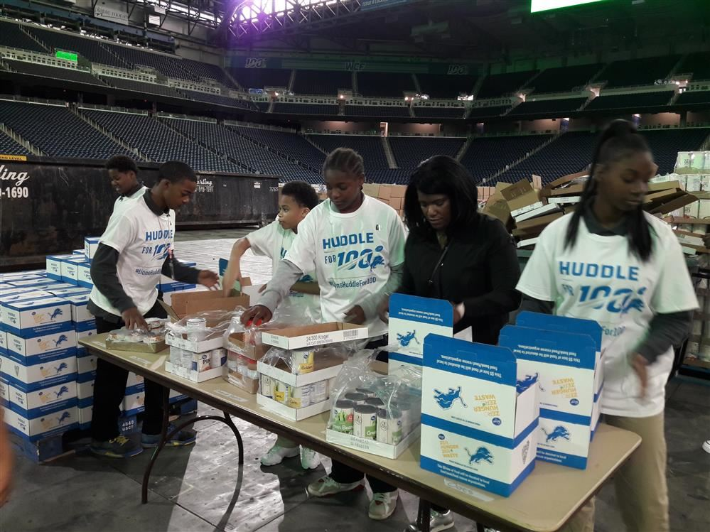 Principal Alean King and students packing food boxes at Ford Field