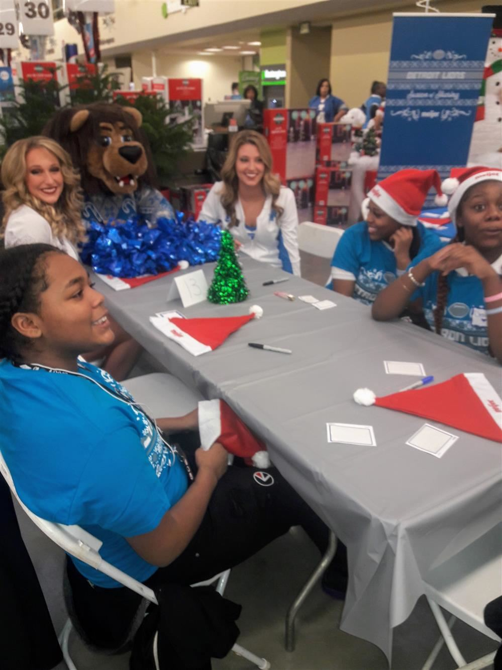Students sitting with Detroit Lions Cheerleaders at Meijer