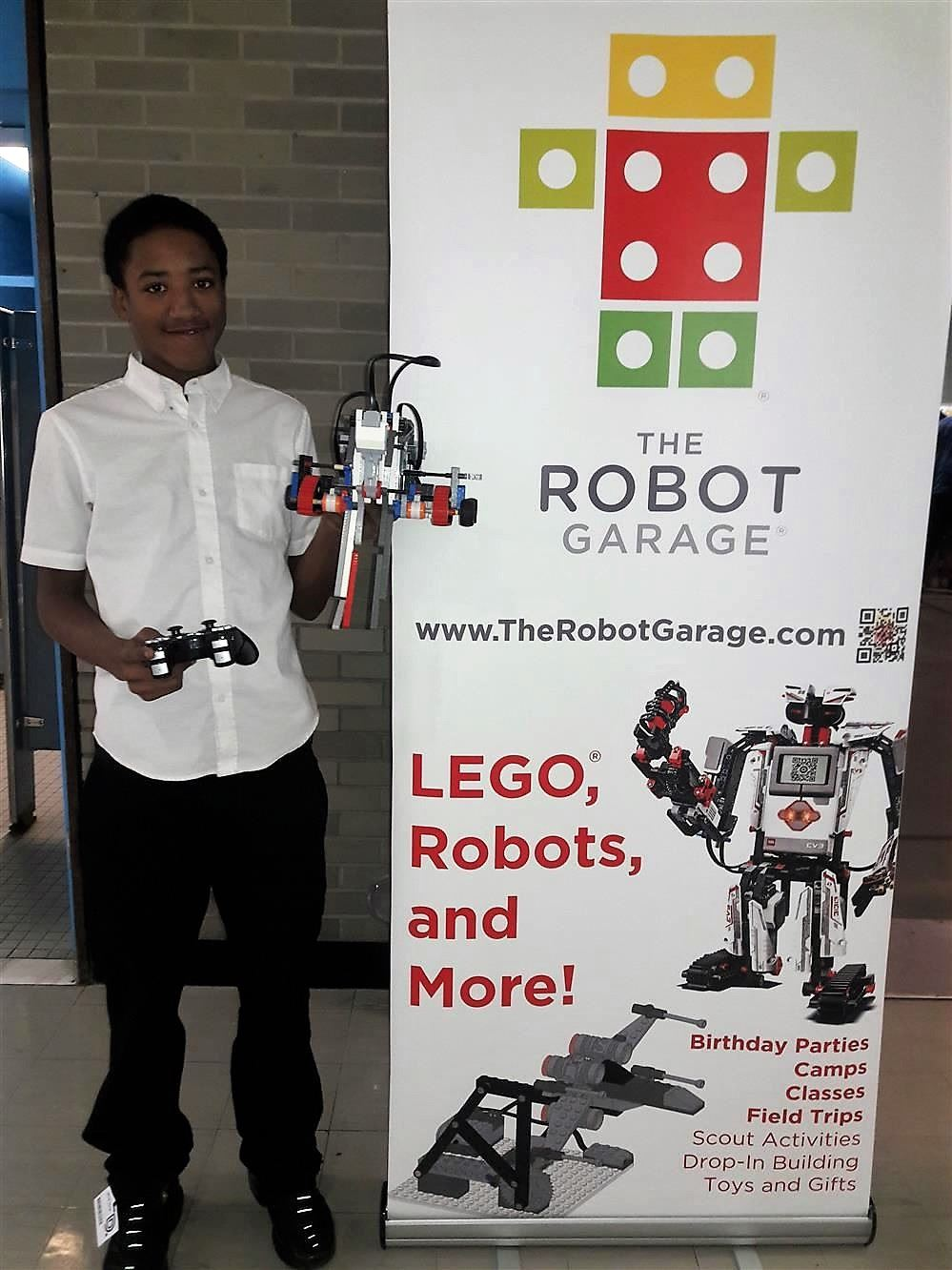 Student holding his team's robot next to a Robot Garage sign