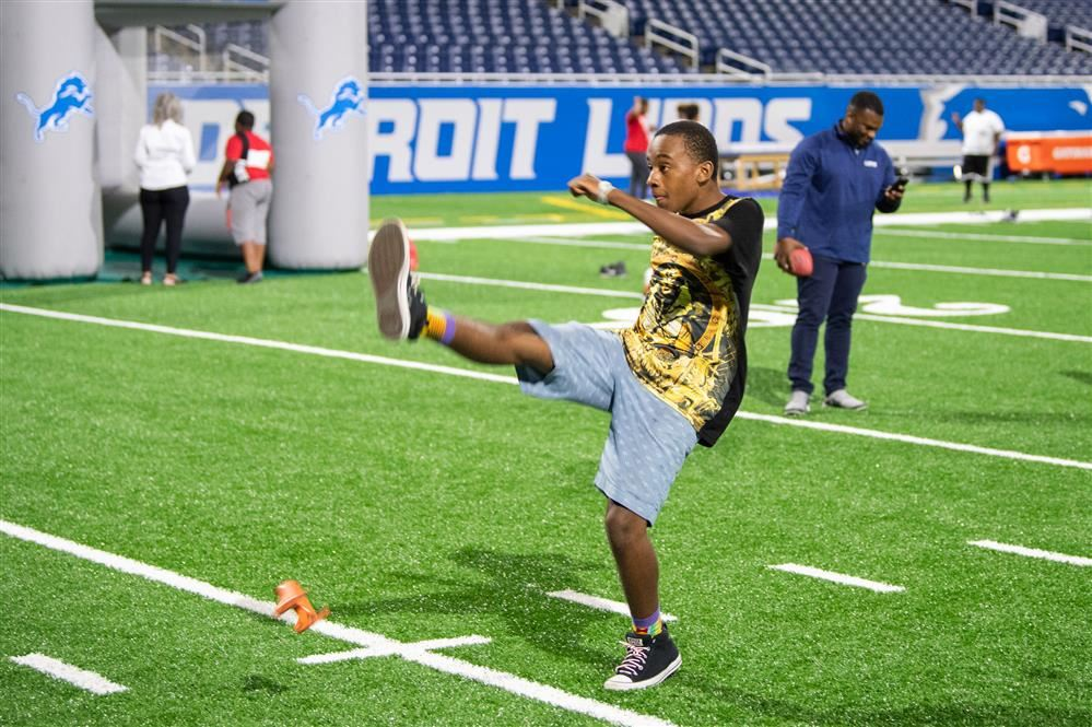 Jamil Harper kicking a football on Ford Field