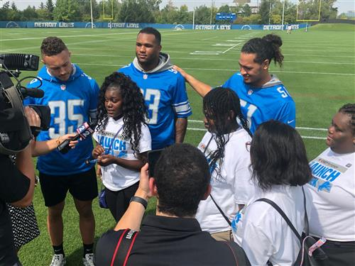 Destinne Taylor and Detroit Lions NFL players doing a news interview