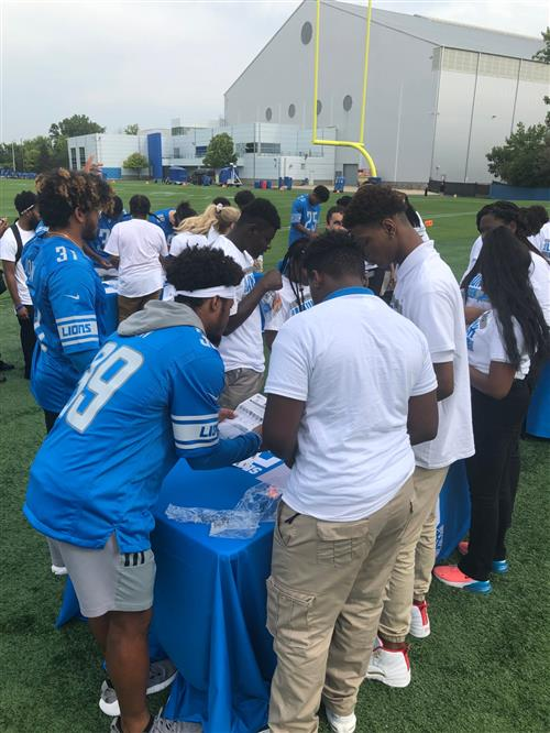 Students and Detroit Lions players assembling the rockets