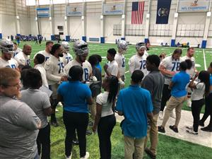 Students talking to the Detroit Lions out on the practice field