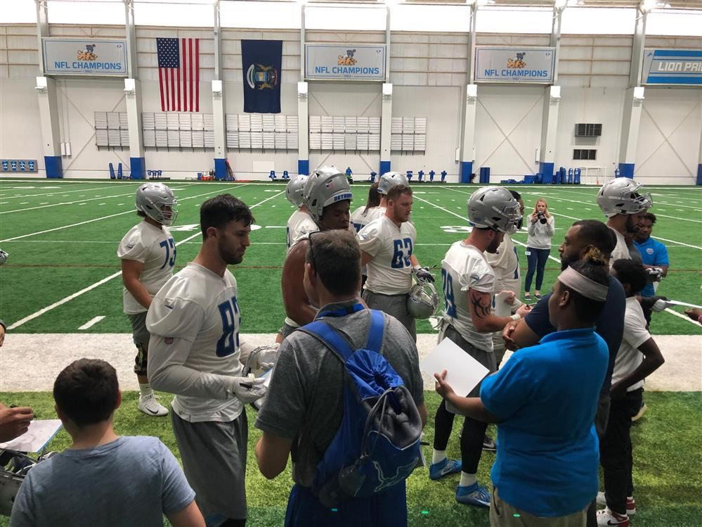 Students out on the field with players at the Detroit Lions practice facility