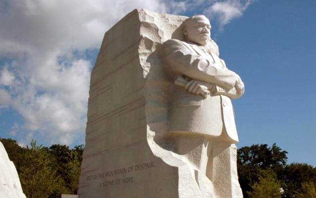 Stone monument of Martin Luther King, Jr. with arms folded.