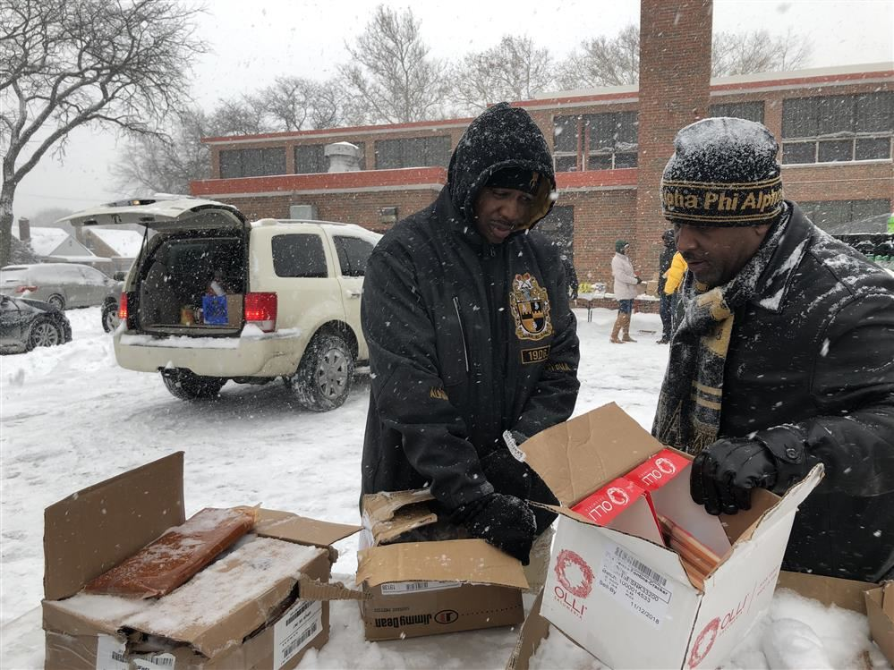 Two Alpha Phi Alpha Fraternity, Incorporated members sort boxes of food in ice cold temperatures.