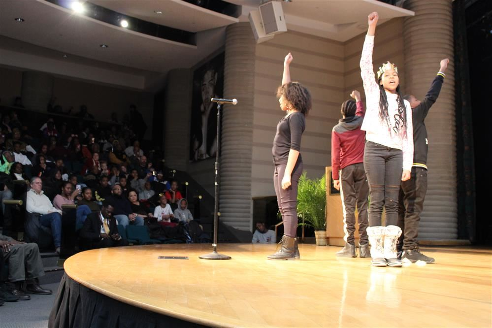 Dosisn students perform spoken word poetry on stage at the Charles H. Wright Museum.