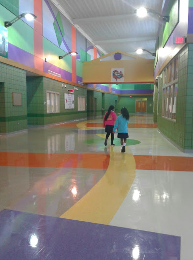two students walking down the colorful main hall at Earhart