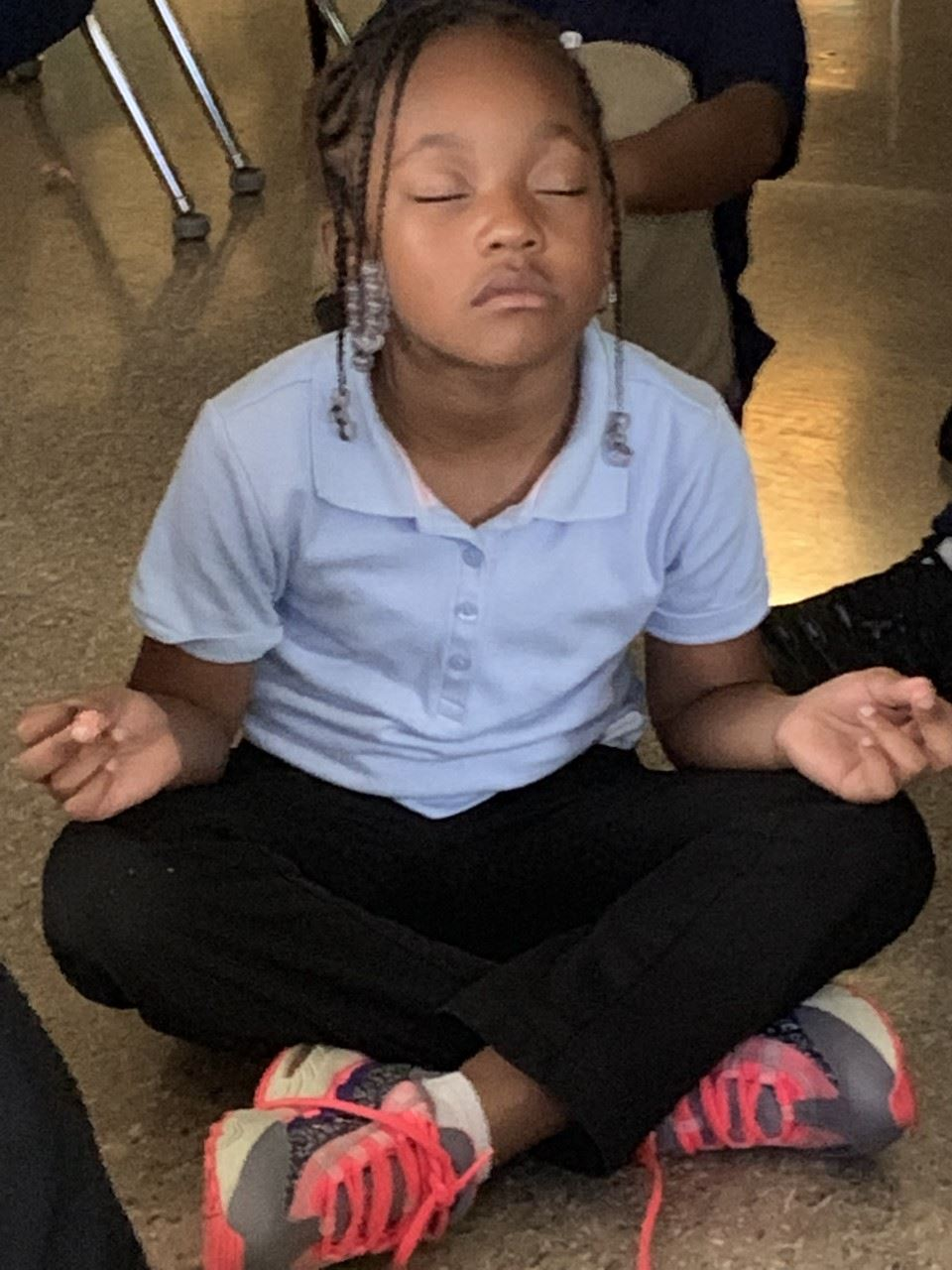 Girl with legs fold, eyes closed in lotus position