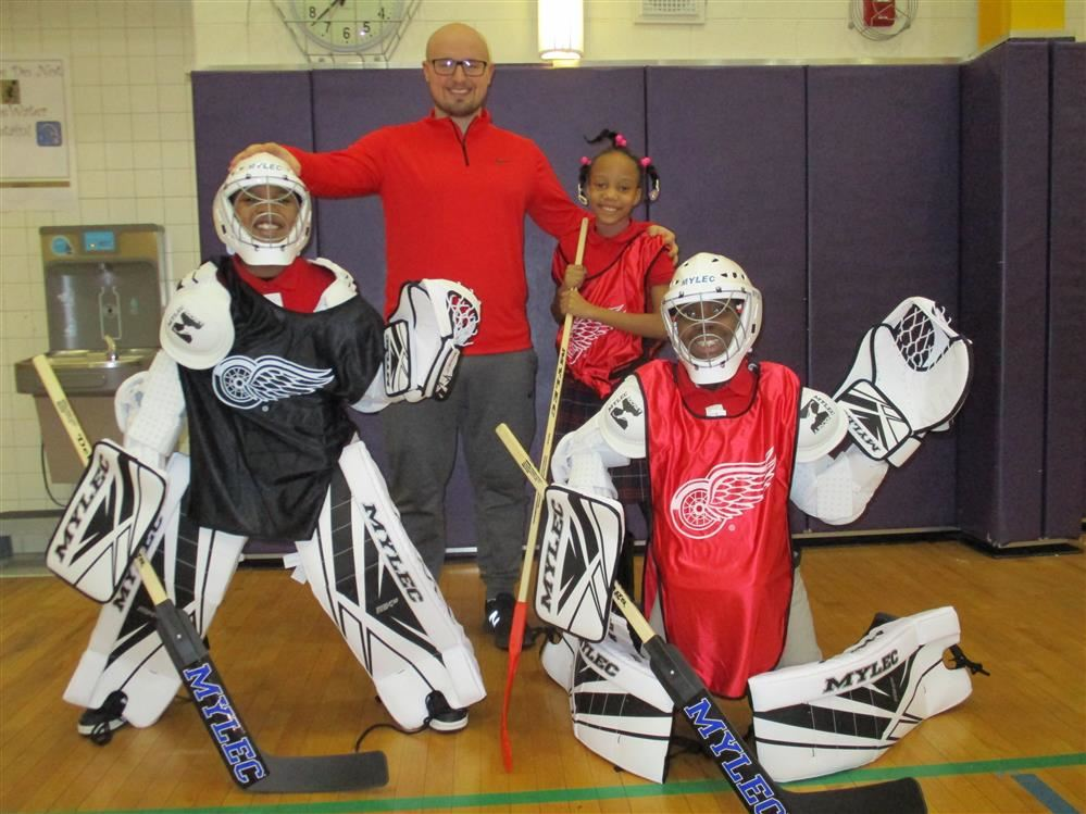 Mr. Kelly and students with hockey equipment