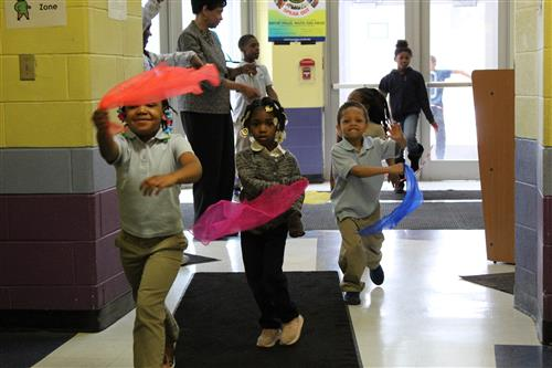 Our wonderful students are twirling their sashes during exercise time while Mrs. Stokes watches.