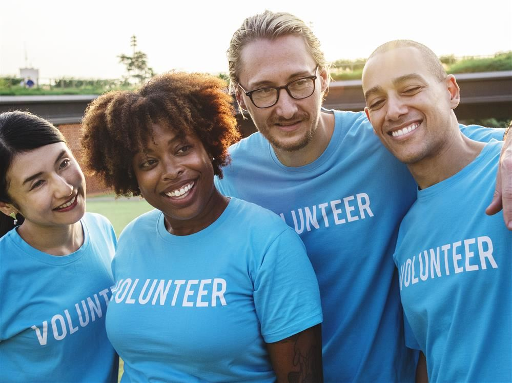 Picture with four people of all races with the word volunteer on their shirts