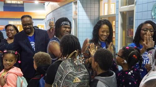Members of the Pistons organization giving high fives to students
