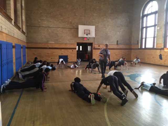 Students exercising with Gym teacher instructing