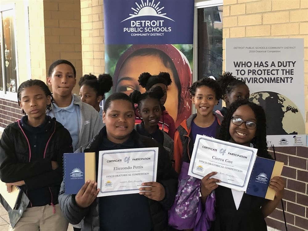 Fifth graders holding up participation certificates