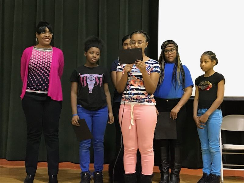 Teacher Ms. Shaw and middle school honor students reciting a poem