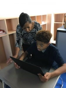 Assistant Principal Mrs. Lane helps a student with a coding exercise